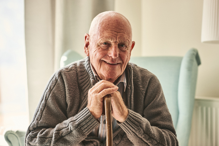 Happy senior man in a sweater with hands crossed over a cane